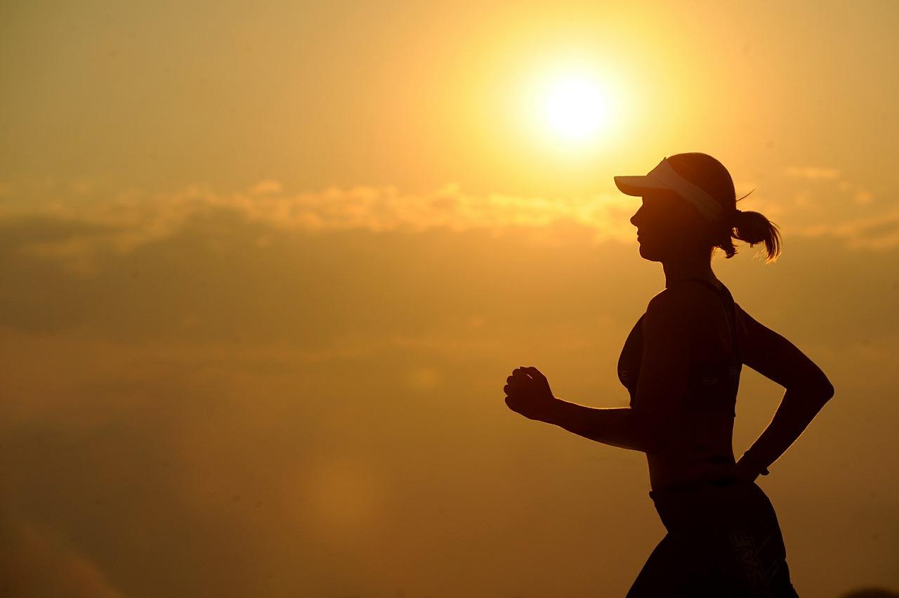 kobieta biegnąca na tle zachodzącego słońca